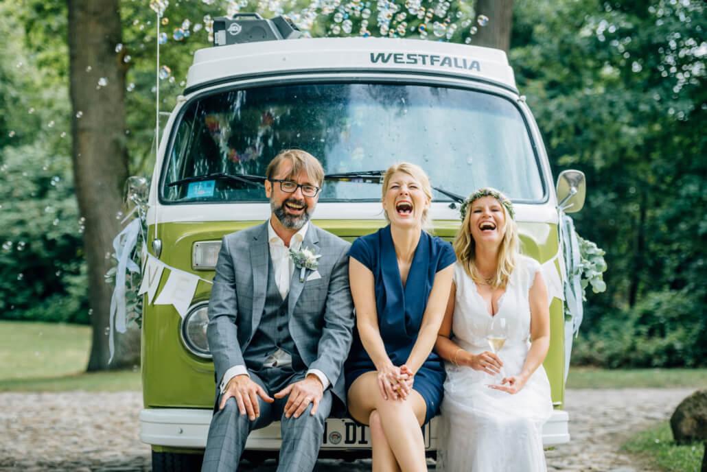 Kirsten sitzt mit Brautpaar Anna und Maik auf der Stoßstange eines VW Busses